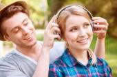 Handsome man putting headphones on pretty girl — Stock Photo