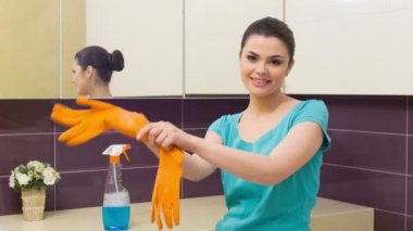 Young woman putting on orange gloves — Stock Video
