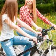 Pretty girls posing with bikes in park — Stock Photo #74014449
