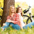 Two girls on a picnic with bikes — Stock Photo #74014709