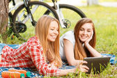 Two girls on a picnic with bikes — Stock Photo