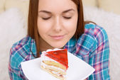 Close-up of girl smelling cake. — Stock Photo