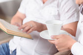 Close-up of family reading book and drinking tea. — Stock Photo