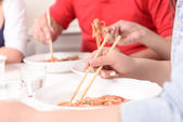 Asians eating with sticks. — Stock Photo