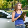 Pretty lady standing with tablet near car — Stock Photo #74594125