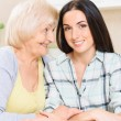Grandmother and granddaughter sitting in kitchen — Stock Photo #74640069