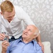 Grandson giving glass with water to grandfather — Stock Photo #75302175