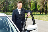 Businessman standing near opened car — Stock Photo