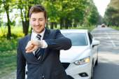 Young businessman checking time near car — Stock Photo