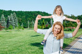 Mother holding her daughter on shoulders — Stock Photo