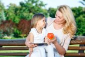 Anne kızı ile bankta tablet kullanma — Stok fotoğraf