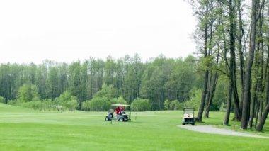 Golf cars on green field — Stock Video