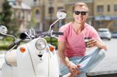 Handsome man sitting with coffee near his scooter — Stock Photo