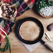 Panqueques en una sartén y productos sobre la mesa — Foto de Stock