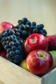 Apples and grapes in a wooden box, close up, selective focus — Zdjęcie stockowe