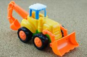 Tractor backhoe toy on sand background. — Stock Photo