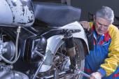 Mechanic tightening a motorbike absorbe — Stock Photo