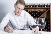 Male winemaker examining a wine glas — Stock Photo