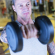 Man making dumbbell front raises - workout routine — Stock Photo #66365431