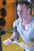 Man making pulley pushdown - workout routine — Stock Photo