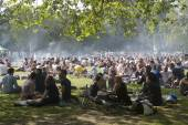 LONDON, UK - MAY 30: Young people are fried kebabs and rest in a local park in Hackney on May 30, 2014 in London, UK. — Stock Photo