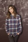 Sad teenager girl in chequered shirt and jeans standing near bro — Stock Photo