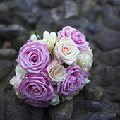 Wedding bouquet of pink and white roses lying on roadway — Stock Photo