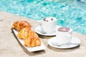 Två koppar kaffe med latte art och croissanter — Stockfoto