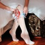White garter on the leg of the bride — Stock Photo #56844231
