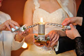Bride and groom lighting candle — Stock Photo