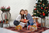 Brother and sister under the Christmas tree with gifts — Stock Photo