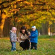Mother with children twins on a walk in the autumn park — Stock Photo #63580637