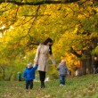 Mother with children twins on a walk in the autumn park — Stock Photo #63581335