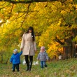 Mother with children twins on a walk in the autumn park — Stock Photo #63581353