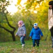 Mother with children twins on a walk in the autumn park — Stock Photo #63581371
