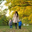 Mother with children twins on a walk in the autumn park — Stock Photo #63581479