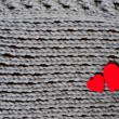 Handmade grey knitting wool texture background with red hearts — Stock Photo #66816457
