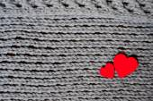 Handmade grey knitting wool texture background with red hearts — Stockfoto
