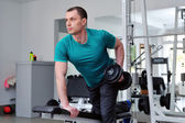 Image of fitness guy in gym exercising with dumbbells — Stock Photo