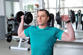 Man lifting dumbbells in a fitness club — Stock Photo
