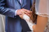 Bride putting a wedding ring on a groom's finger — Stock Photo