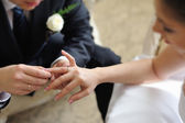 Groom putting ring on bride's finger — Stock Photo
