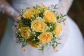 Bride with a bouquet in the arms of the groom — Stock Photo