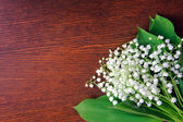 Bouquet of lilies of the valley on the wooden board — Stock Photo