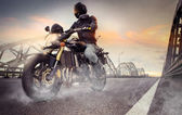 Biker riding motorcycle — Stock Photo