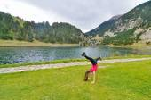 Teenage girl doing acrobatics in front of a lake — Stock Photo
