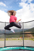 Teenage girl jumping on a trampoline — Stock Photo