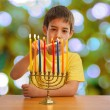 Israeli boy lighting a Hannukah Menorah — Stock Photo #61658129