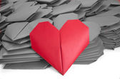 A red paper heart in a pile of grey ones for Valentine's Day — Stock Photo