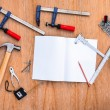 Collection of worktools, set of working tools. (Steel wrench, hammer, nails, bolts, wrenches, etc.) with notebook on the wooden table. — Stock Photo #77828104
